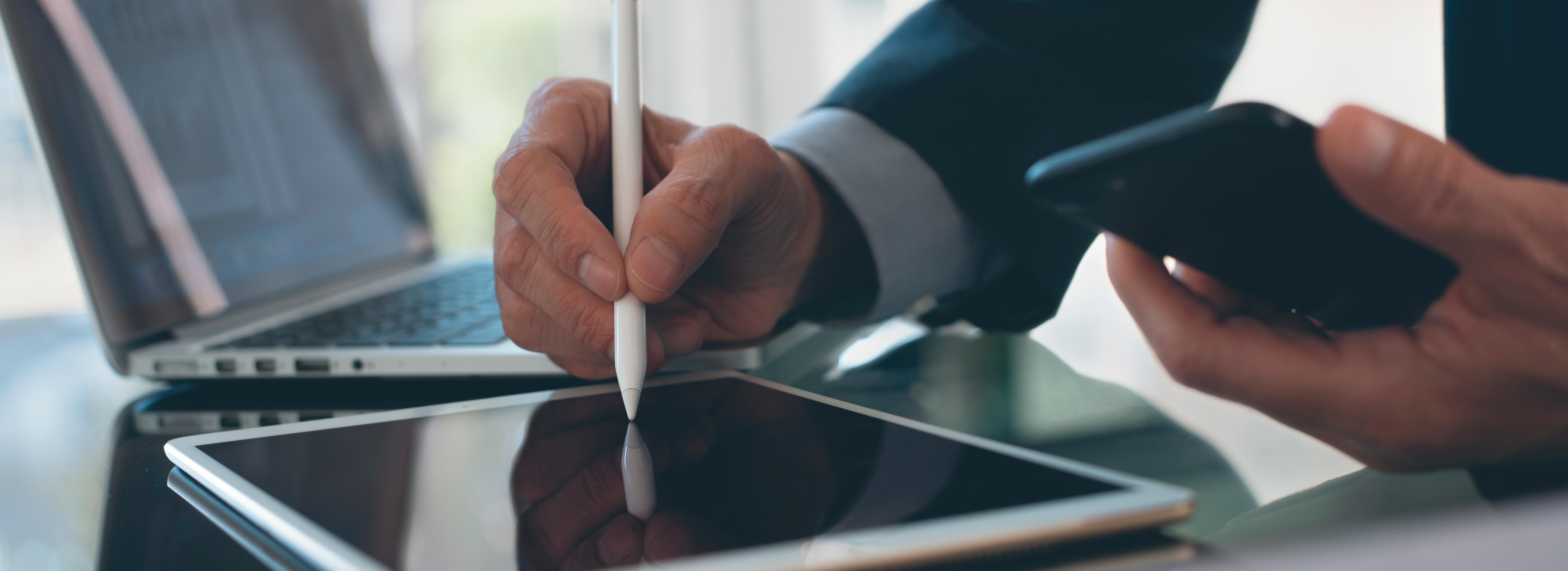 A imagem mostra um homem de negócios assinando um documento eletrônico