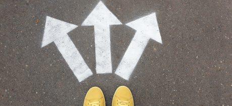 A imagem mostra os pés de uma pessoa sobre setas desenhadas no chão indicando diferentes caminhos