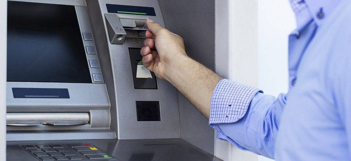 Hand of man with credit card, using a ATM